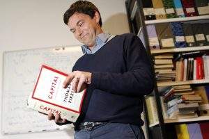 Thomas Piketty, French economist and academic, poses in his book-lined office at the French School for Advanced Studies in the Social Sciences (EHESS), in Paris
