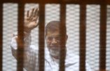 Egypt's deposed Islamist president Mohamed Morsi waves inside the defendant's cage during a trial at the police academy in Cairo on December 7, 2014. An Egyptian court sentenced to death four members of the blacklisted Muslim Brotherhood over the killing of protesters who stormed the group's Cairo headquarters in June last year. Decisions on 14 other defendants in the case, including Muslim Brotherhood chief Mohamed Badie and his deputies Khairat al-Shater and Saad al-Katatni, will be made at the next hearing on February 28, the official said. AFP PHOTO / AHMED RAMADAN